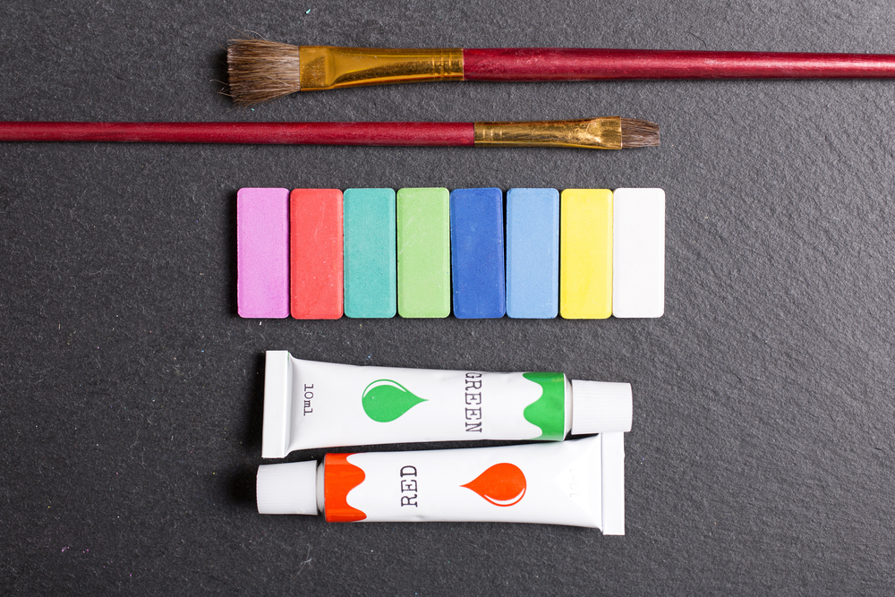 Selection of red green paint oils with brushes on a black slate surface